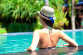 Back view of beautiful woman in straw hat in luxury pool — Stock Photo