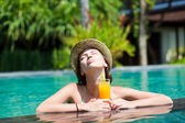 Beautiful woman in straw hat with fresh juice in luxury pool — Stock Photo