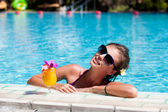 Beautiful girl in sunglasses with fresh mango juice in luxury po — Stock Photo