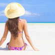 Back view of young woman in straw hat with closed eyes on the beach — Stock Photo