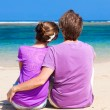 Back view of young happy couple sitting on tropical beach. honeymoon concept — Stock Photo #22298771