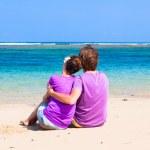 Vista posterior de joven pareja feliz en la playa tropical. concepto de luna de miel — Foto de Stock