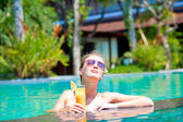 Beautiful girl in sunglasses with fresh mango juice in luxury pool — Stock Photo