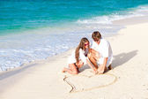Young happy couple drawing heart on tropical beach. honeymoon — Stock Photo