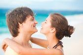 Retrato do jovem casal feliz se divertindo em uma praia tropical. lua de mel — Fotografia Stock