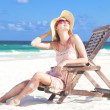 Young woman in straw hat and bikini sitting on beach chair — Stock Photo