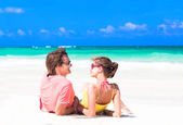 Young couple lying on sand under sunny summer sun — Foto Stock