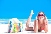 Woman in bikini with beach bag enjoying her vacation — Stock Photo