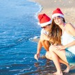 Young couple in santa hats laughing on tropical beach. new year — Stock Photo #35212893