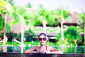 Portrait of young attractive smiling woman in luxury pool — Stock Photo