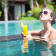 Beautiful girl with orange juice in luxury pool — Stock Photo