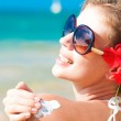 Young woman in sunglasses putting sun cream on shoulder — Stock Photo