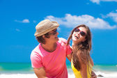 Closeup of happy young couple in sunglasses on beach smiling — Stock Photo
