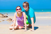 Closeup of happy young couple in sunglasses sitting on beach smiling — Stock Photo