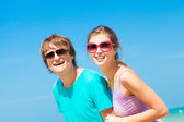 Closeup of happy young couple in sunglasses on beach smiling — 图库照片