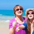 Closeup of happy young couple in sunglasses smiling. Thumbs up — Стоковое фото