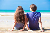 Young happy couple sitting on tropical beach — Stock Photo