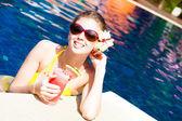Beautiful girl in sunglasses with fresh fruit juice in luxury pool — Stok fotoğraf