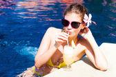 Beautiful girl in sunglasses drinking fresh fruit juice in luxury pool — Stock Photo