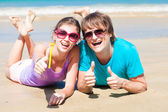 Closeup of happy young couple in sunglasses lying on beach smiling — Stock Photo