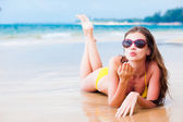 Long haired girl in sunglasses blowing a kiss on tropical beach — Stock Photo
