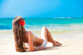 Long haired woman with flower in hair in bikini on tropical beach — Stock Photo