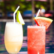 Stock Photo: Two glasses of cocktails with fruits near pool