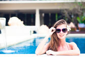 Portrait of young attractive smiling woman with flower in hair in luxury pool — Stock Photo