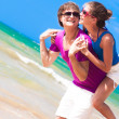 Happy couple piggybacking cheerful on beach on vacation — Stock Photo #39648587