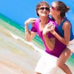 Happy couple piggybacking cheerful on beach on vacation — Stock Photo