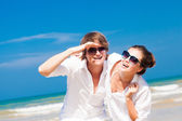 Closeup of happy young couple in white clothes having fun smiling on beach — Stock Photo