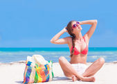 Young woman in bikini and sunglasses with beach bag sitting on beach — Stock Photo