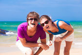 Couple in sunglasses smiling on beach — Stock Photo