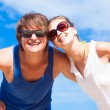 Closeup of happy young couple in sunglasses smiling on tropical beach — Stockfoto
