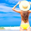 Closeup back view young long haired womin yellow bikini and straw hat on beach — Stock Photo #41854379