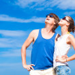 Happy young couple in sunglasses smiling pointing to sky — Stock Photo #41854555