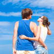 Stock Photo: Happy young couple in sunglasses smiling pointing to sky