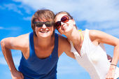 Closeup of happy young couple in sunglasses smiling on tropical beach — Stock Photo