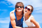 Closeup of happy young couple in sunglasses having fun on tropical beach — Stock Photo