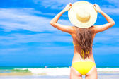 Closeup back view young long haired woman in yellow bikini and straw hat on beach — Stock Photo