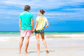 Back view of couple holding hands on tropical beach in sunglasses in Thailand — Stock Photo