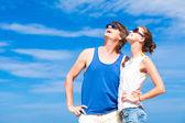 šťastný mladý pár v sluneční brýle s úsměvem, ukazující k obloze — Stock fotografie