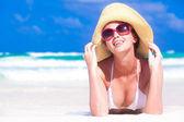 Front view of beautiful young woman in sunglasses and straw hat lying on beach enjoying the sun — Stock Photo