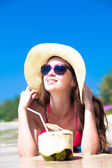 Portrait of young woman lying in straw hat in sunglasses with coconut on beach — Stock Photo