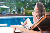 Happy young woman in bikini laying on chaise-longue luxury pool side — Stockfoto