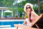 Happy young woman in bikini laying on chaise-longue air kiss — Stockfoto