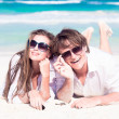 Stock Photo: Portrait of happy young couple in sunglasses in white clothes lying on beach smiling