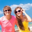 Stock Photo: Closeup of happy young caucasicouple in sunglasses smiling on beach