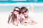 Portrait of happy young couple in sunglasses in white clothes lying on beach smiling — Stock Photo