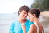 Portrait of happy young couple flirting on tropical beach in the evening — Stockfoto